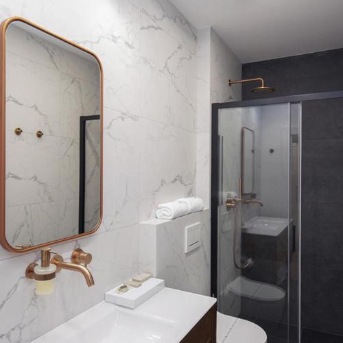 W łazience w hotelu zgodnie z projektem wykonanym przez naszych projektantów zastosowano stylizowaną szafkę pod umywalką oraz marmurowe płytki.